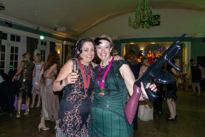 Two ladies posing on the dance floor at the Speakeasy Gatsby party