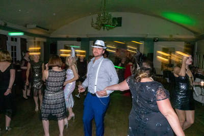 Man in hat dancing with women in Gatsby themed outfits