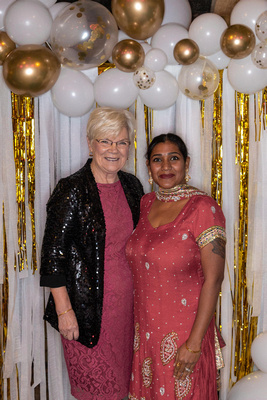 mother-in-law and daughter-in-law with gold and white balloon backdrop photo booth